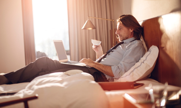 A man relaxing on a hotel bed