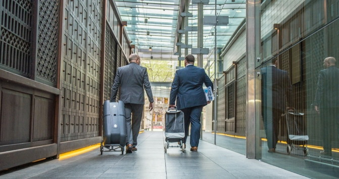 Two men pulling luggage