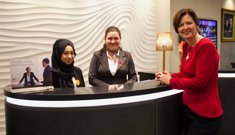 Employees and a guest at a hotel reception desk