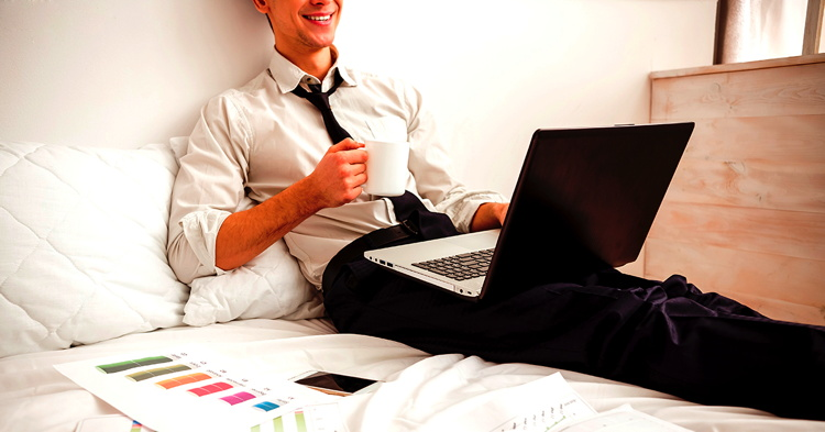 A man on a hotel bed using a laptop