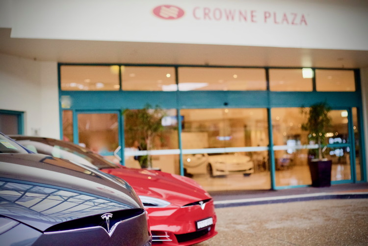 Teslas parked in front of a Crowne Plaza Hotel