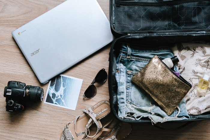 A suitcase, laptop and other travel items - Photo by Anete Lūsiņa on Unsplash