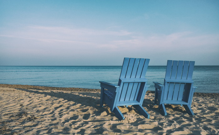 Pair of wooden blue beach chairs on the sand beach - Photo by Aaron Burden on Unsplash