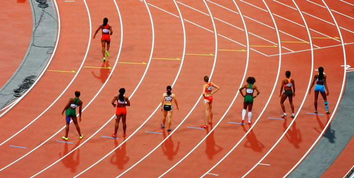 A woman running on a race track while seven others stand back and stretch - Photo by Matt Lee on Unsplash