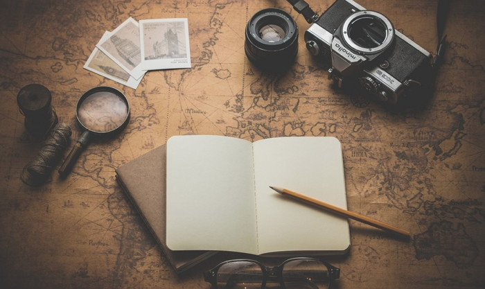A camera, notebook, photos etc on top of a large map - Unsplash - Dariusz Sankowski