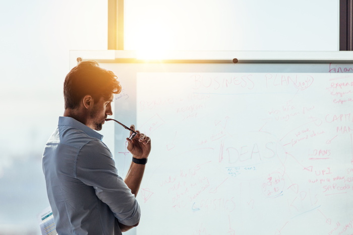 A man in front of a white board
