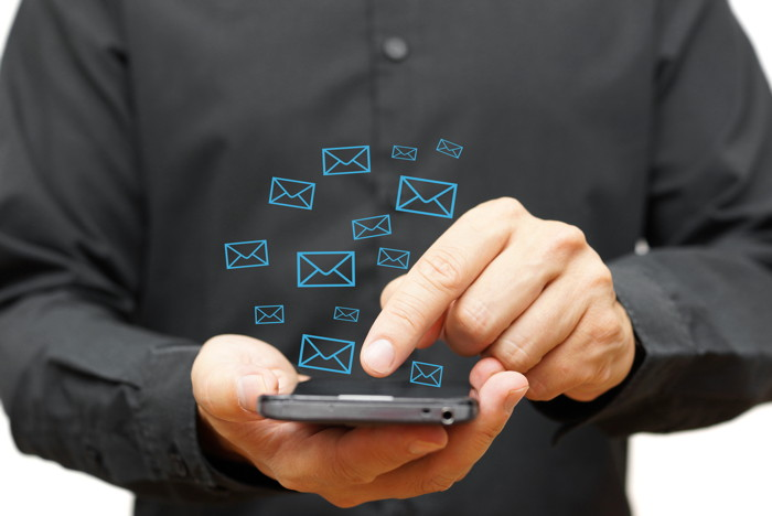 A man with a mobile phone and floating email icons