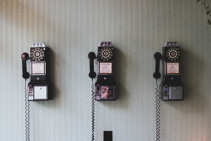 Three vintage olden days telephone hanging on the wall for public use - Photo by Pavan Trikutam on Unsplash