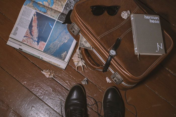 An overhead view of a person's shoes next to a leather suitcase with a book on it and a tourist guide under it - Photo by Damir Bosnjak on Unsplash