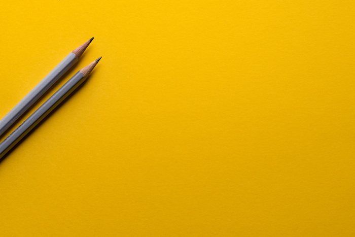 Two gray pencils on a yellow surface - Photo by Joanna Kosinska on Unsplash