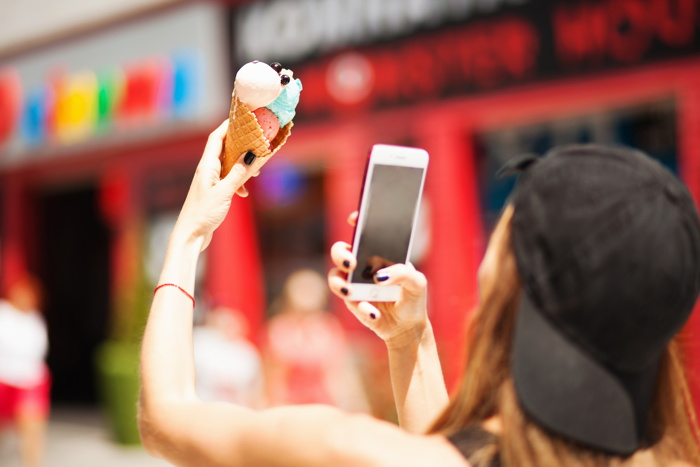 A woman taking a picture of an ice cream cone