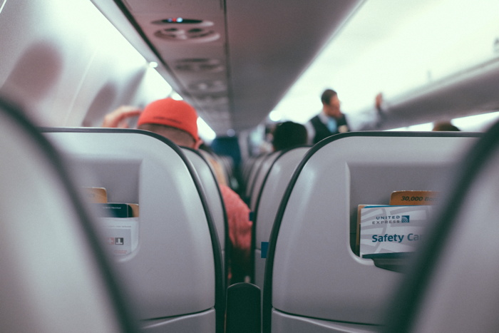 Sitting in an airplane seat as people board their flight - Photo by Gus Ruballo on Unsplash