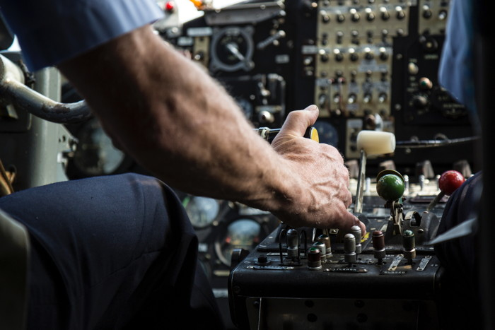 person operating black audio mixer in an airplane cockpit - Photo by Laurent Perren on Unsplash