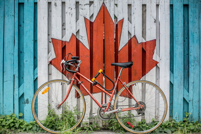 red road bike beside red and white wooden maple leaf painted wall - Photo by Ali Tawfiq on Unsplash