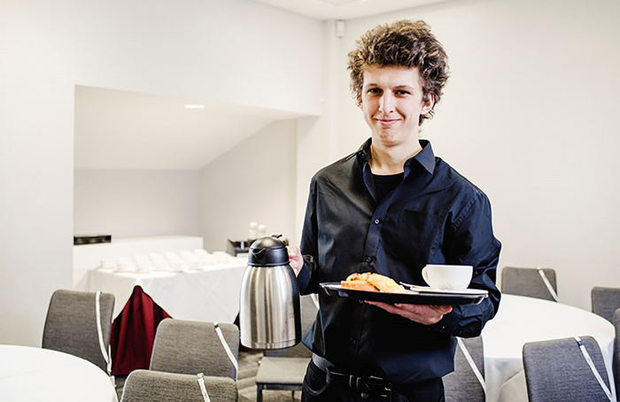 A young man serving coffee in a meeting room