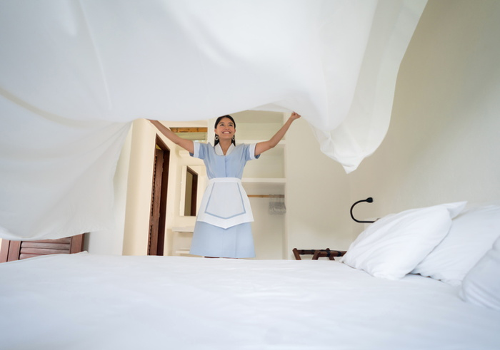 A room attendant making a hotel bed