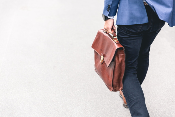 person walking holding brown leather bag - Photo by Marten Bjork on Unsplash