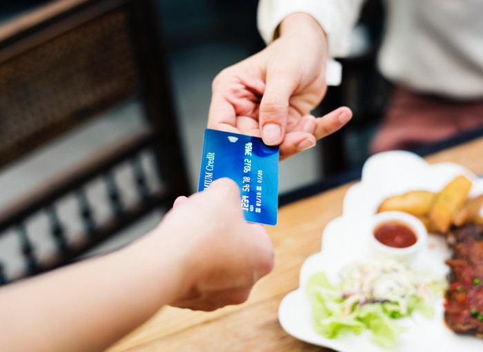 Person holding a credit card - Photo by rawpixel on Unsplash