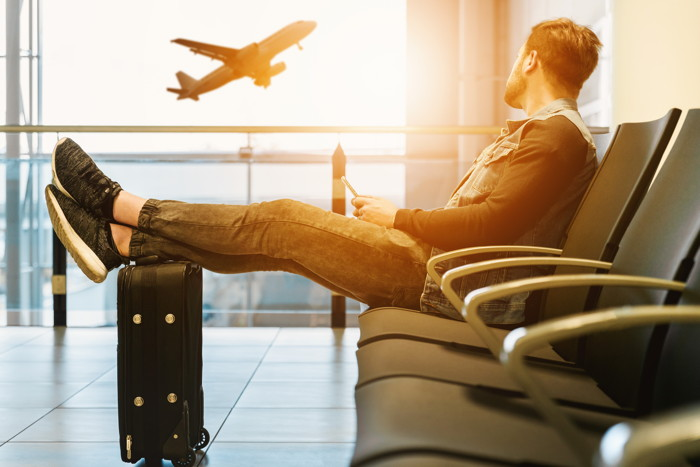 Man sitting on gang chair with feet on luggage looking at airplane - Photo by JESHOOTS.COM on Unsplash