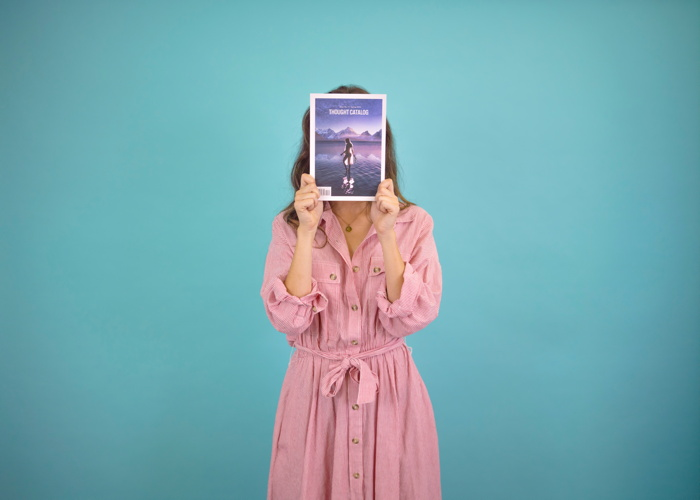 Woman wearing pink dress covering her face with book - Photo by Thought Catalog on Unsplash