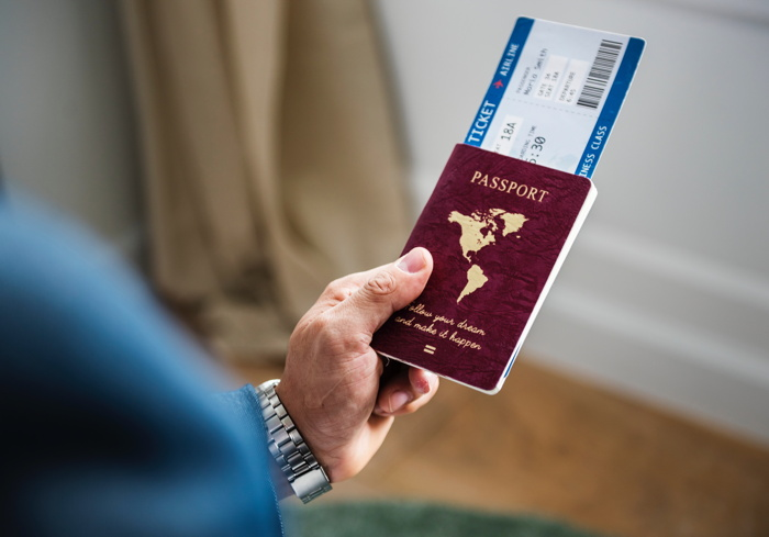 Person holding passport - Photo by rawpixel on Unsplash