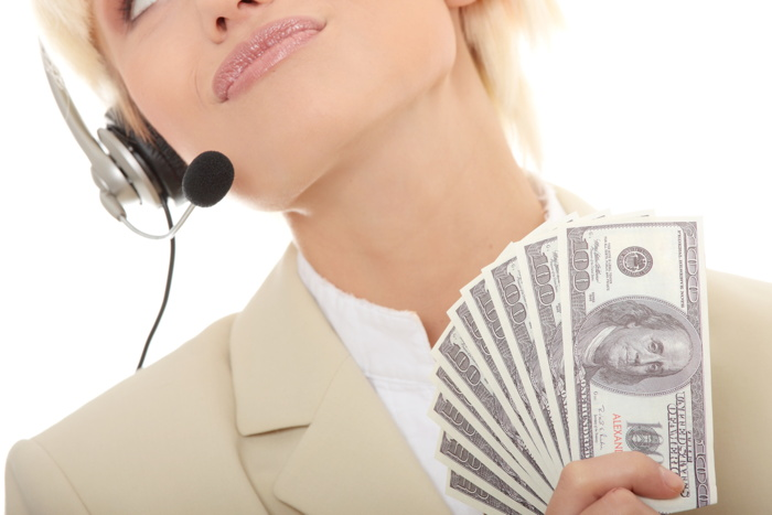 A woman with a headset and money in her hand
