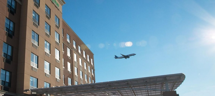 Holiday Inn Hotel at JFK Airport - Exterior with an airplane in the background