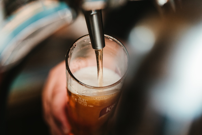 person filling beer glass - Photo by Bence Boros on Unsplash