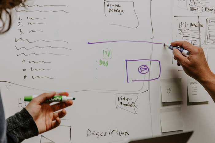 two people drawing on whiteboard - Photo by Kaleidico on Unsplash