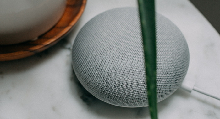 Google Home Mini speaker near plant pot on white surface - Photo by Charles Deluvio on Unsplash