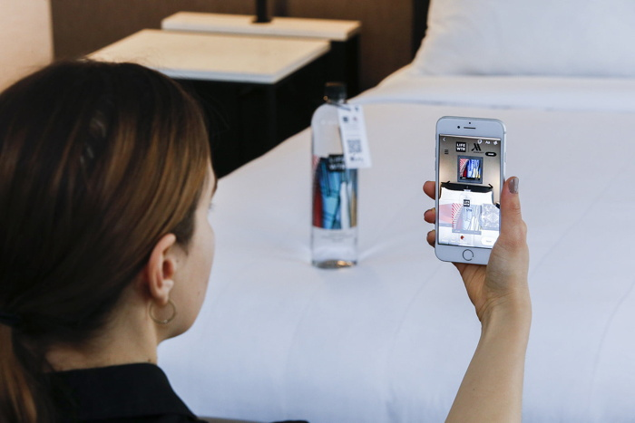 A woman using the LIFEWTR/Marriott app