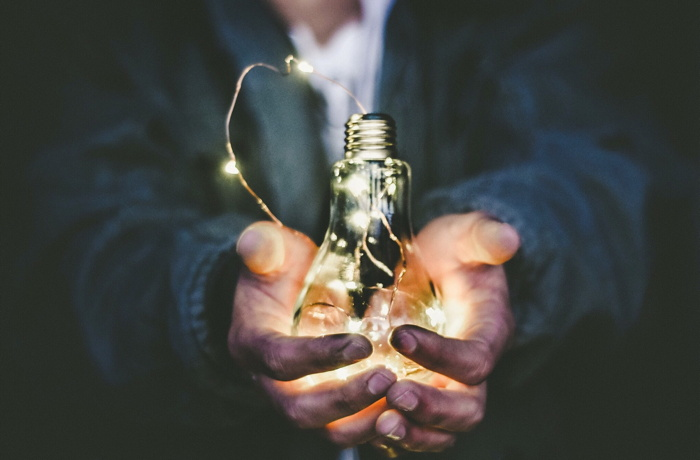 man holding incandescent bulb - Photo by Riccardo Annandale on Unsplash