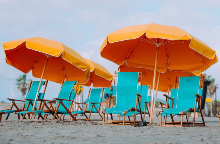 closeup photo of lounger chairs and beach umbrellas - Photo by Annie Spratt on Unsplash