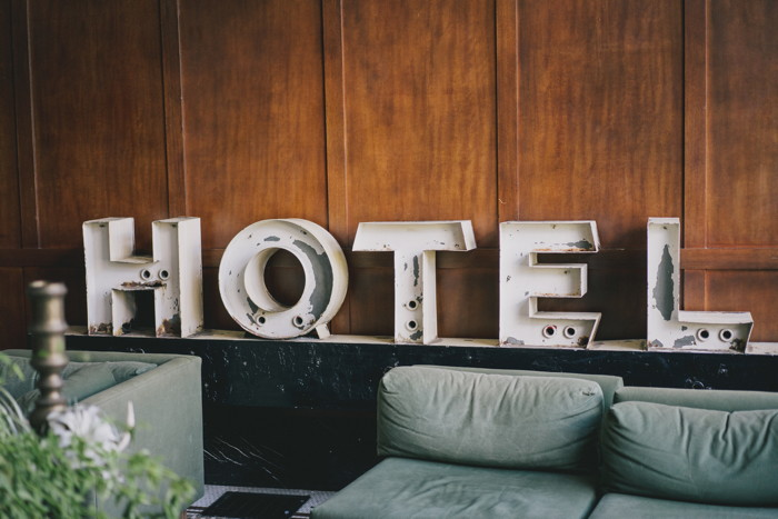 white Hotel signage near sofa - Photo by Bill Anastas on Unsplash