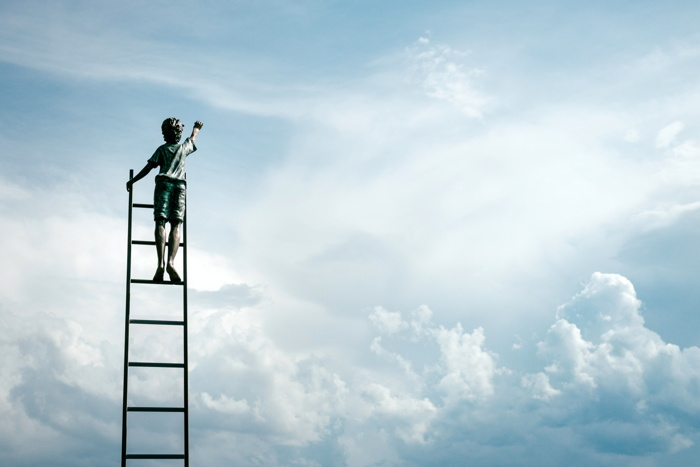 boy standing on ladder reaching for the clouds - Photo by Samuel Zeller on Unsplash