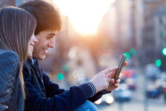 A young couple looking at a smart phone