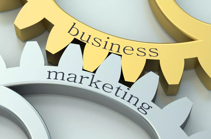 Two cogs with the words business and marketing