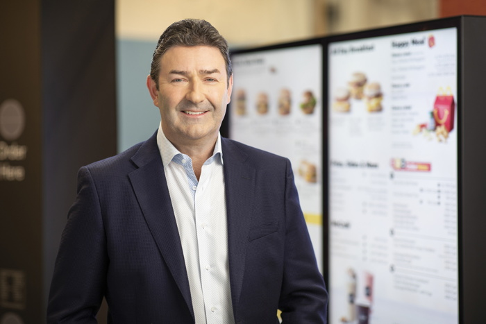 McDonald's President and Chief Executive Officer Steve Easterbrook pictured in front of a drive-thru digital menu board