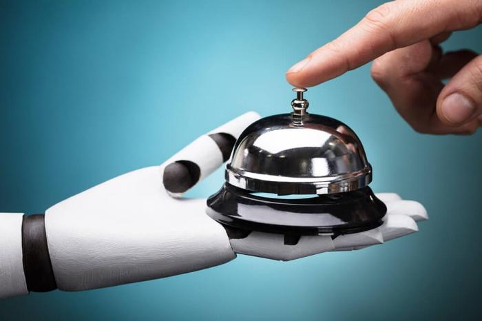 A robot hand holding a desk bell