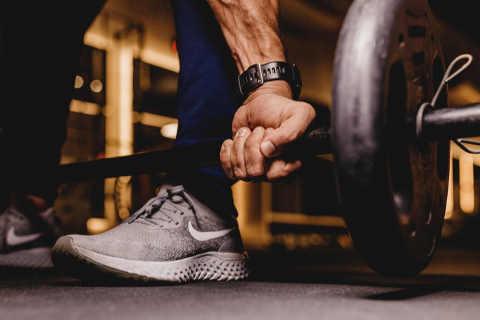 person about to lift barbell - Photo by Jonathan Borba on Unsplash