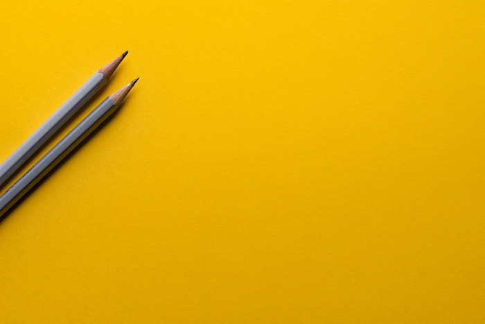 two gray pencils on yellow surface - Photo by Joanna Kosinska on Unsplash