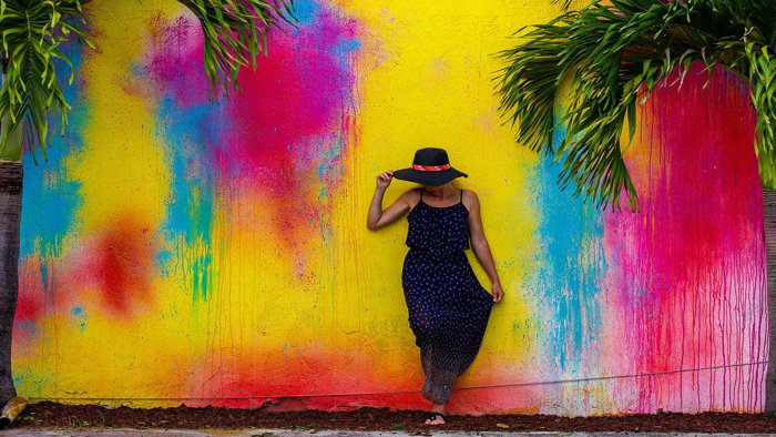 A woman in front of a colorful wall