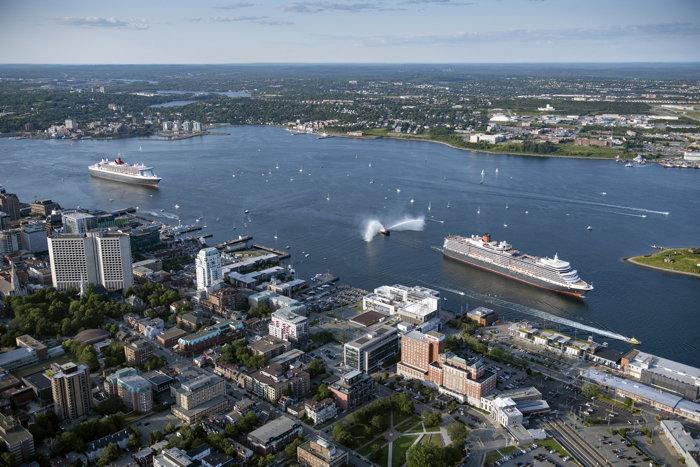 Cunard's flagship ocean liner Queen Mary 2 follows sister ship Queen Elizabeth in Halifax, Nova Scotia harbor on Friday, July 26, 2019. (Photo Credit: Steve Farmer for Cunard)