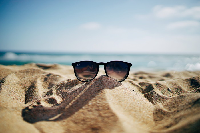 black Ray-Ban Wayfarer sunglasses on beach sand - Photo by Ethan Robertson on Unsplash