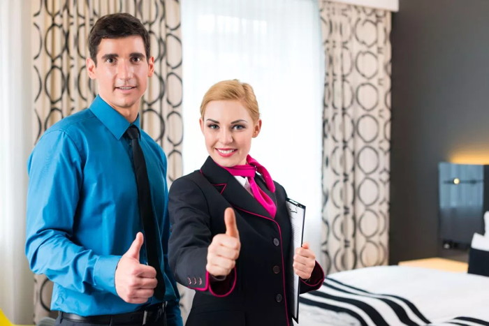 A man and a woman looking at the camera with thumbs up