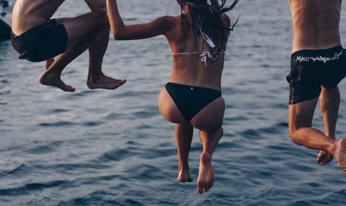 one woman and two men jumping at sea