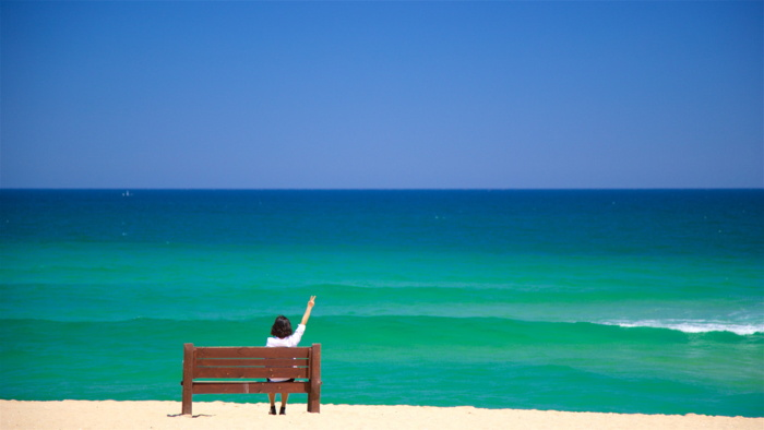 A woman sitting on a bench at the beach