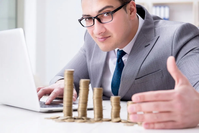 A man with a stack of coins on his desk