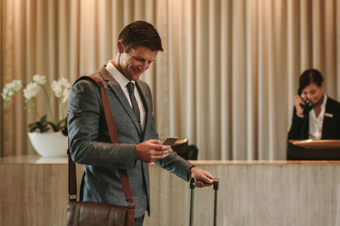 A man in a hotel lobby looking at his phone