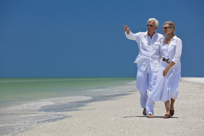 A mature couple walking on a beach